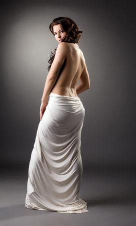 erotic woman: Back view of slender brunette posing at camera, on gray background