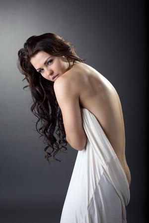 donna nuda: Bella bruna ricci posa curva a porte chiuse. Studio di fotografia