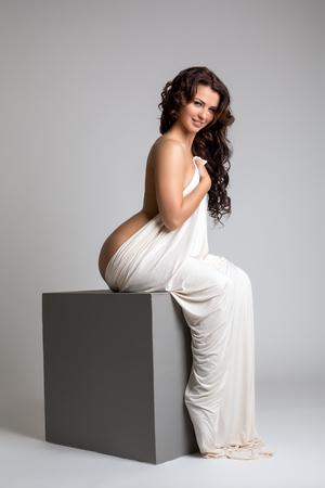 sex pose: Studio shot of smiling nude brunette posing sitting on cube Stock Photo