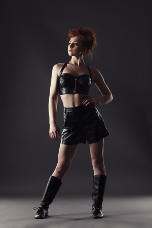 leather boots: Confident red-haired dancer posing in leather costume