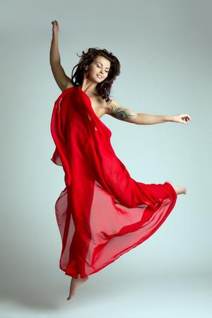 Bevallige vrouwelijke danser stellen in sprong. Studio foto