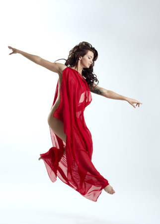 Studio shot of pretty brunette jumping in dance photo