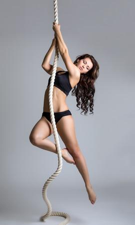 Gymnastics. Beautiful brunette training on rope photo