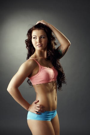 Sport. Sexy fitness girl posing in studio, on grey background Stock Photo