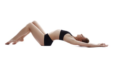 Graceful athletic girl lying in studio, isolated on white background