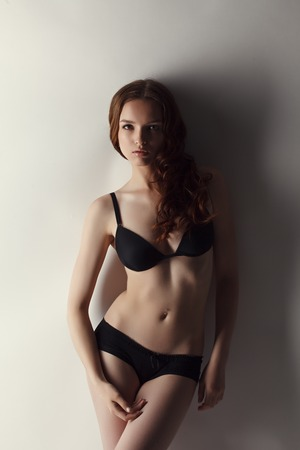 advertises: Attractive brown haired model advertises underwear. Studio photo