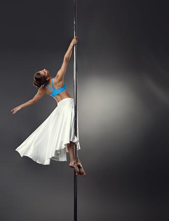 harmonous: Studio shot of dreamy woman dancing on pole in studio