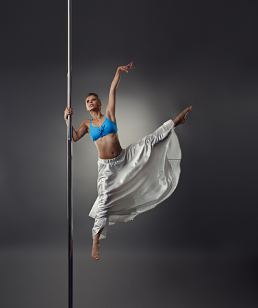 harmonous: Image of strong and graceful girl dancing on pylon