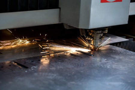 Image of modern automated machine laser cutting metal sheet