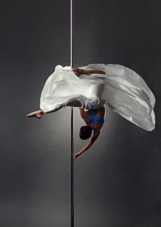 harmonous: Strong female dancer froze in difficult position on pylon