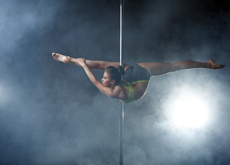 Flexible girl posing in difficult stretching position on pole