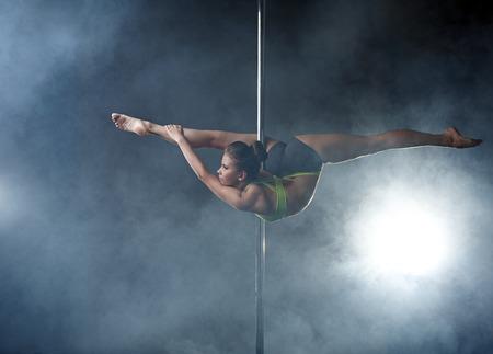 Flexible Mädchen posiert in schwierigen Reckposition auf der Pole Standard-Bild - 44694934