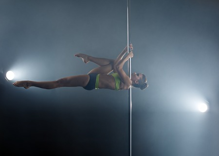 Flexible girl dancing on pole in rays of spotlights