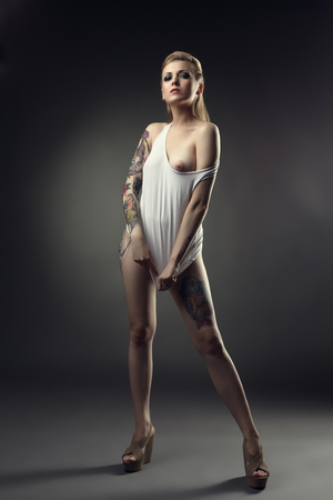 Creative tattooed model posing with naked breast, on grey backdrop Stock Photo