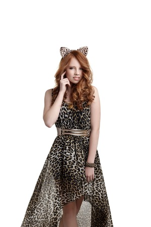 catwoman: Charming red-haired girl posing in catwoman outfit, isolated on white