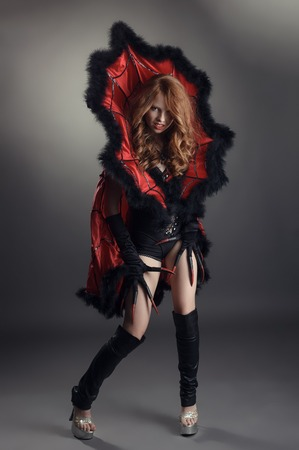 black and red: Beautiful redhead girl posing dressed up for Halloween Stock Photo