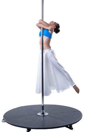 harmonous: Graceful girl dancing on pylon. Studio photo, isolated over white backdrop