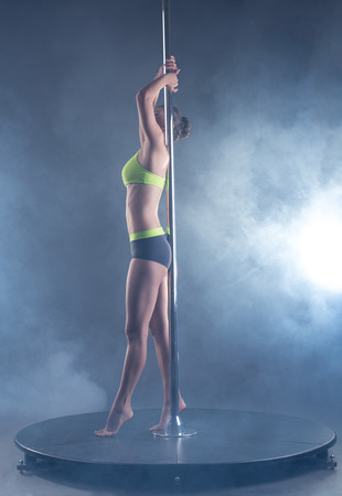 stripper pole: Pole dance. Harmonous girl posing on background of spotlights Stock Photo