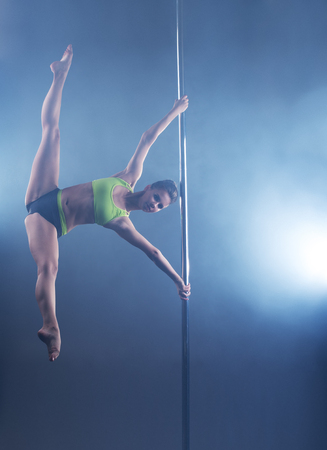 pole dance: Pole dance. Strong female dancer froze in stretching pose Stock Photo