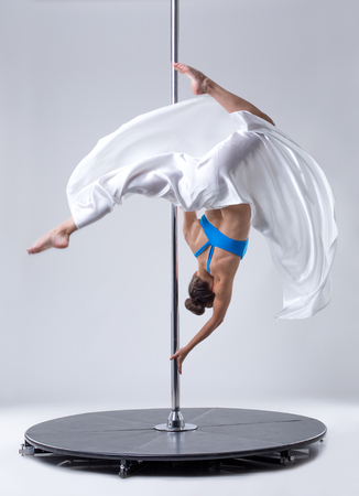 harmonous: Sexy female dancer hanging upside down on pole Stock Photo