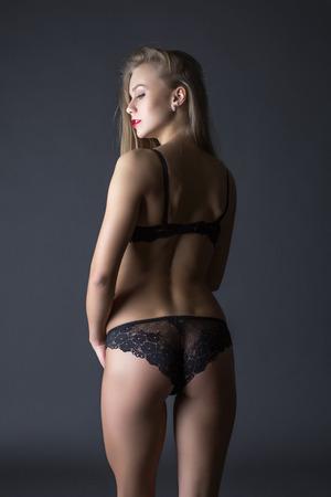 mujeres eroticas: Vista posterior de la esbelta belleza posando en ropa interior de encaje