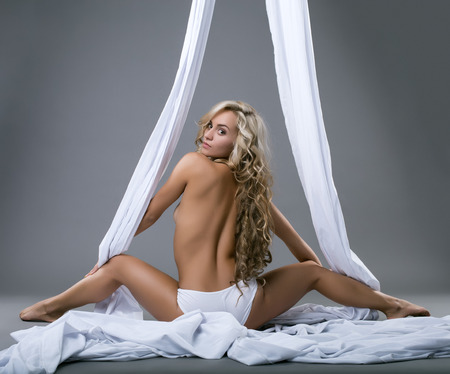 nude blonde woman: Back view of pretty blonde posing topless with aerial silks