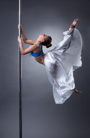 tänzerin: Reizvoller Tänzer drehen anmutig um Pol. Studio Foto, auf grauem Hintergrund