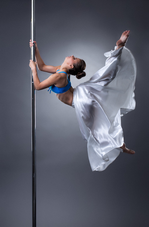 Sexy dancer turning gracefully around pole. Studio photo, on grey background