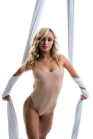 donna che balla: Tessuti aerei. Immagine di seducente bionda in posa a porte chiuse
