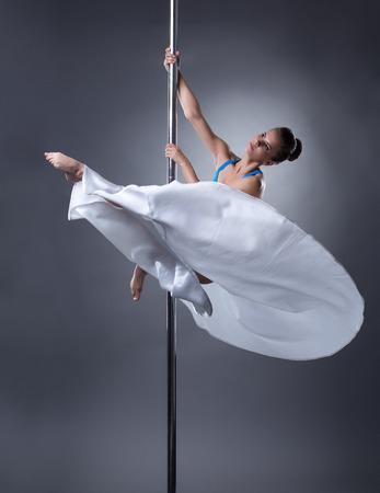 harmonous: Pole dance. Pretty dancer posing in elegant position