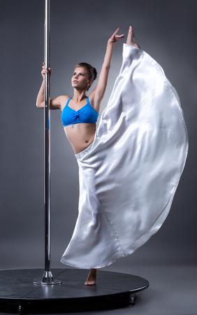 tänzerin: Elegante weibliche Tänzerin posiert am Pylon, auf grauem Hintergrund Lizenzfreie Bilder