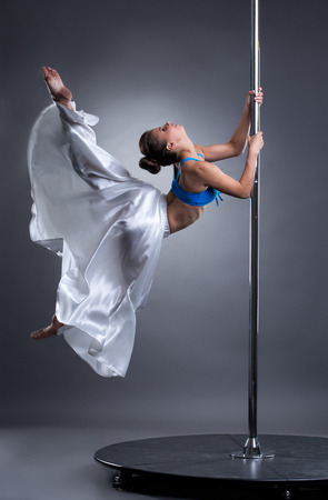 pole dance: Image of beautiful girl turning gracefully around pylon