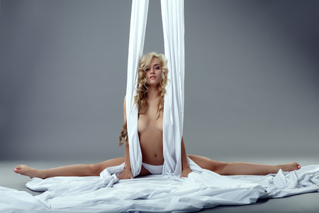 Aerial silk. Image of alluring topless blonde doing split Stock Photo