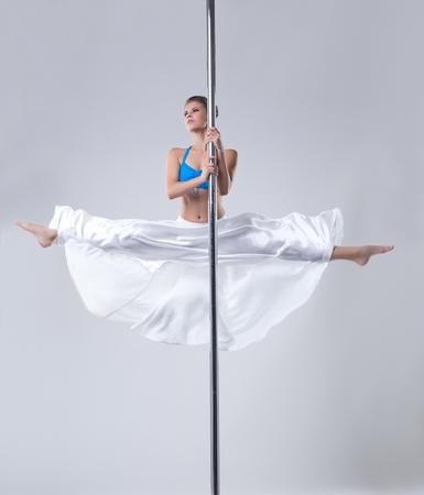 harmonous: Cute girl easily performs gymnastic split on pole. Studio photo Stock Photo