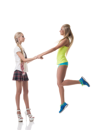 sisters sexy: Sport or study. Girl holding hand of her friend jumping