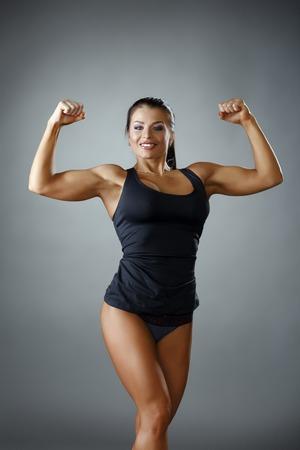 atletismo: Culturista femenina feliz que muestra sus bíceps en la cámara