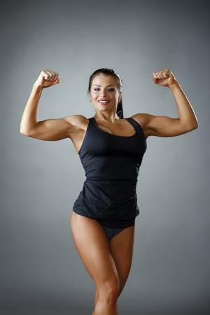 athletics: Happy female bodybuilder showing her biceps at camera