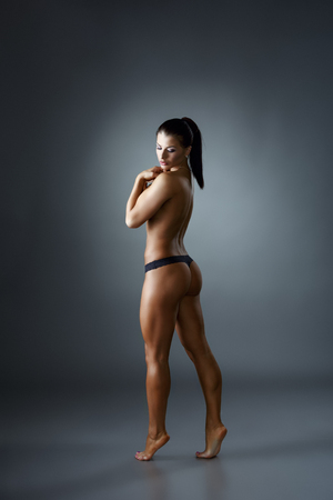topless brunette: Bodybuilding. Pretty topless woman posing back to camera