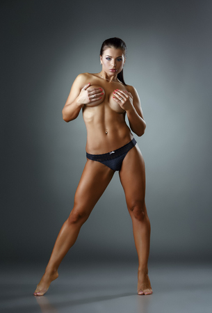 nudo integrale: Bodybuilding. Colpo di donna abbronzata in posa in topless a porte chiuse Archivio Fotografico