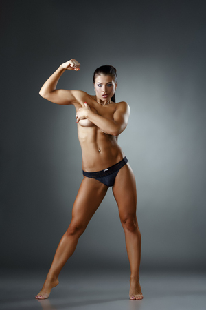 nude women: Studio photo of sexy female bodybuilder showing biceps Stock Photo