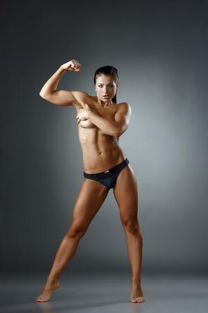 nude woman: Studio photo of sexy female bodybuilder showing biceps Stock Photo