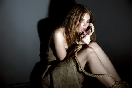 Concept. Kidnapped model asks for help on cellular phone Stock Photo