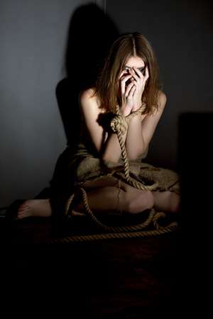 bounded: Kidnapping concept. Pretty girl posing tied with rope Stock Photo