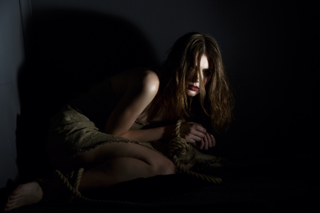 trapped: Concept. Studio photo of frightened model held hostage