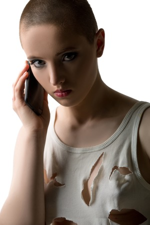 skinhead: Studio portrait of skinhead girl talking on phone Stock Photo