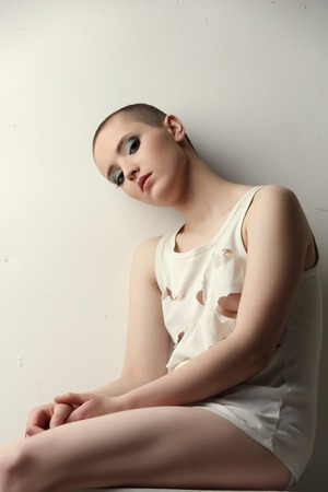 skinhead: Studio shot of pretty skinhead girl in ragged t-shirt