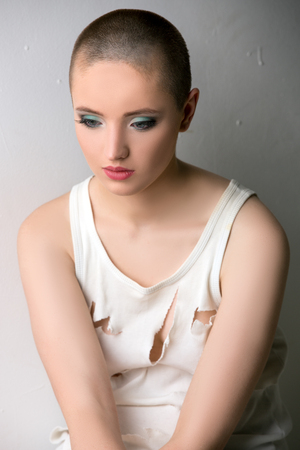 skinhead: Portrait of beautiful skinhead girl in ragged t-shirt Stock Photo