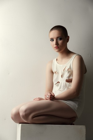 skinhead: Pretty skinhead girl in torn T-shirt posing as crazy Stock Photo