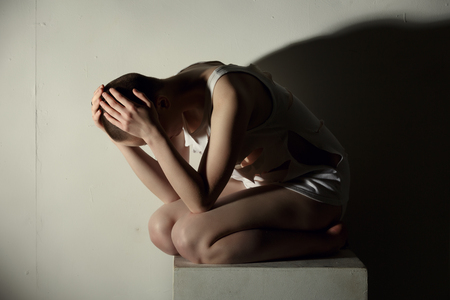 Mental illness. Image of thin girl holding her head