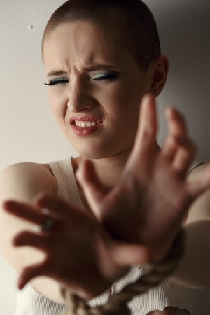 skinhead: Studio portrait of frustrated woman with tied hands